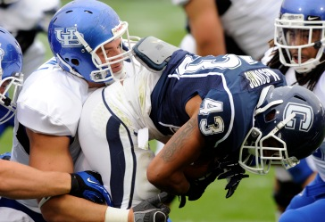 Buffalo's Kristjan Sokoli, left, tackles Connecticut's Lyle McCombs during the first half of Connecticut's 24-17 victory in their NCAA football game in East Hartford, Conn., on Saturday, Sept. 29, 2012. (AP Photo/Fred Beckham)